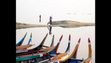 Coloured Prows, Mandalay, by Charlie Waite. Colourful pointed prows of 8 wooden boats pulled up on a lake shore, with water and figures in the distance