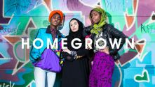 National Youth Theatre: homegrown. Three young women leaning against a colourful graffitied wall