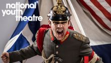 National Youth Theatre Macbeth - photo of shouting soldier with background of flags