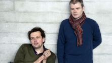 Simon Stephens and Mark Haddon. against a backround of a concrete wall at the NT
