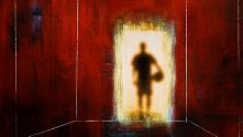 The Red Lion. Blurred figure holding a football in a doorway, lit from behind