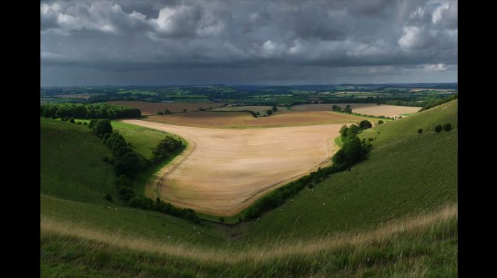 Dorset, Win Green Hill, England, by Charlie Waite. Varied agricultural landscape beneath stormy skies, with a sunlit middle distance