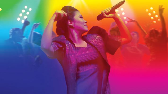 Here Lies Love. Imelda Marcos with a microphone against a vivid coloured background