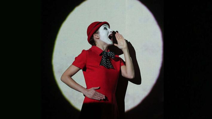 The Animals and Children Took to the Streets. A white-faced mime, gesturing to shout, in a red top, caught in a spotlight against a black background