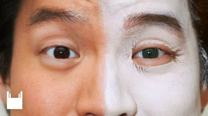 Yellow Face. Close up of a face from forehead to bridge of nose, right side with white make-up