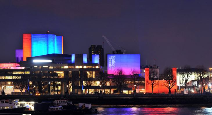 National Theatre with its temporary theatre, seen from the North bank of the Thames by night