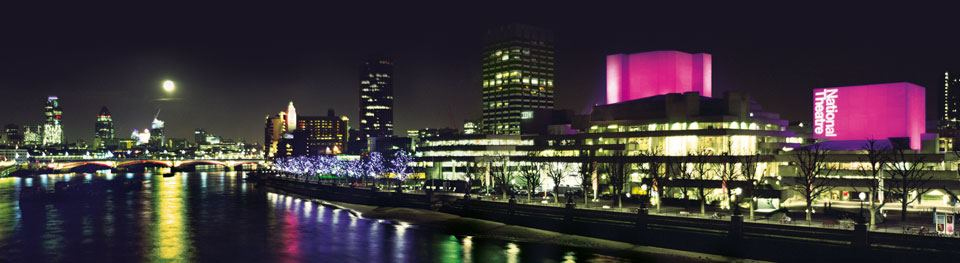 The National Theatre at night, illuminated, with the Thames river