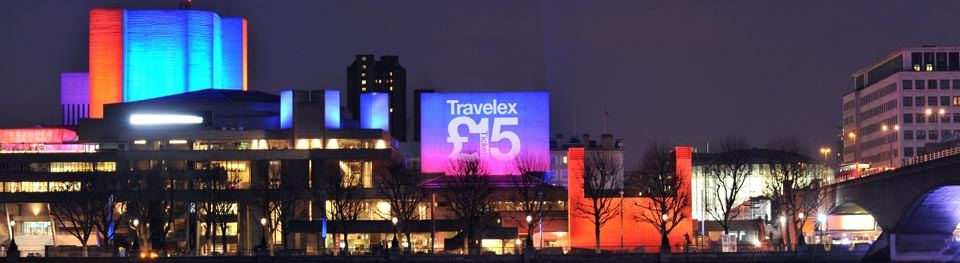 National Theatre at night viewed from north of the river with £15 Travelex tickets logo on the Lyttelton flytower